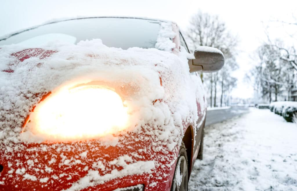 Red car with tire in snow on the side of the road | Marietta Wrecker Service