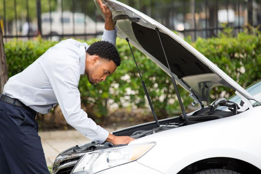 Man Checking Under Hood of Car for Car Start Problem | Marietta Wrecker Service